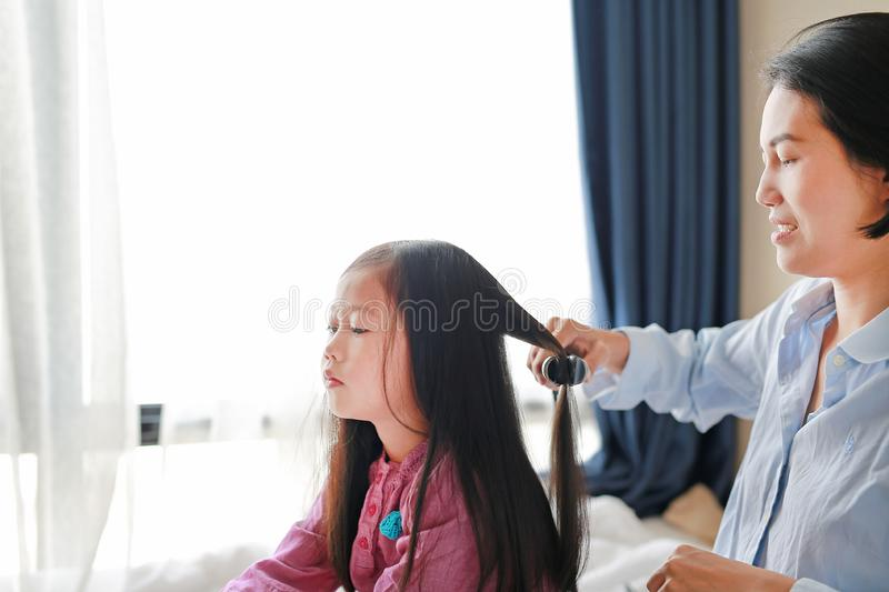 Beautiful little Asian child girl with long hair and mom dressed up for Smooth hair at morning in the room royalty free stock image