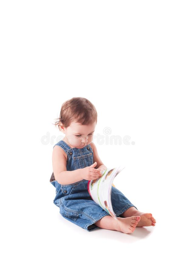 Beautiful little baby with a book stock photography