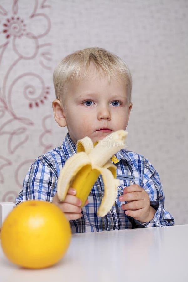 Beautiful little baby boy eats banana royalty free stock images