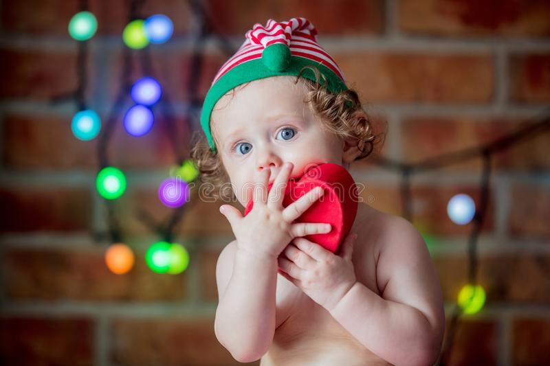 Beautiful little baby boy in elf hat with gift box royalty free stock photos