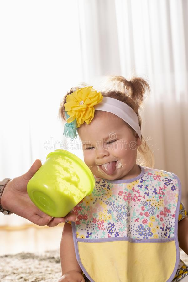 Funny baby girl eating vegetable pap stock images