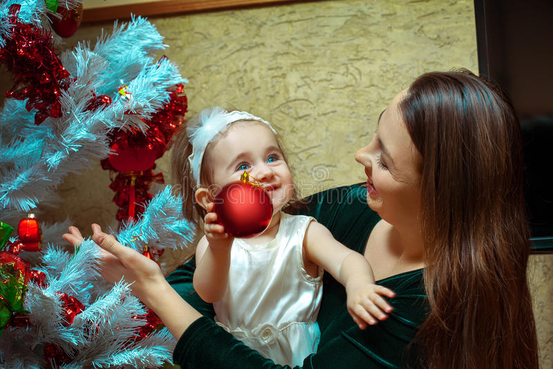 beautiful little baby girl with blue eyes decorates the Christmas tree with her mother stock photography