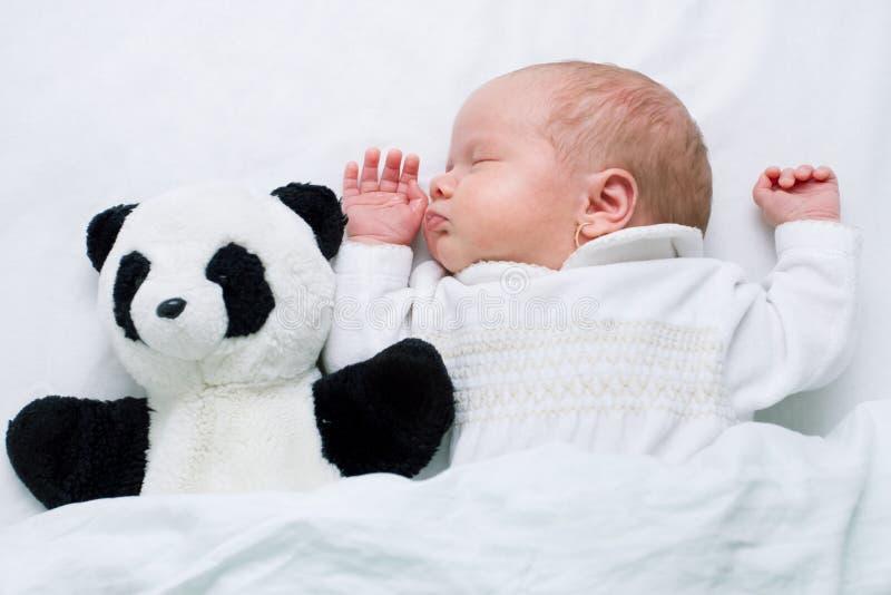 Newborn baby girl - 4 weeks - sleeping together with panda teddy bear stock images