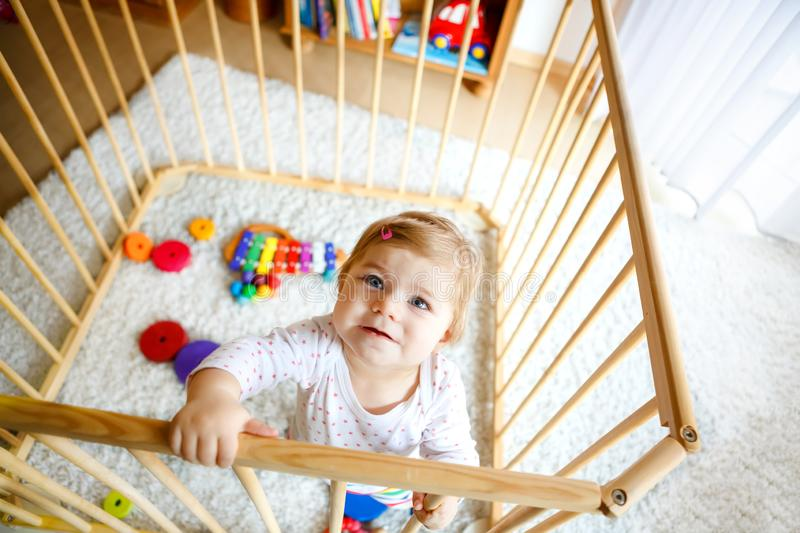 Beautiful little baby girl standing inside playpen. Cute adorable child playing with colorful toys. Home or nursery royalty free stock image