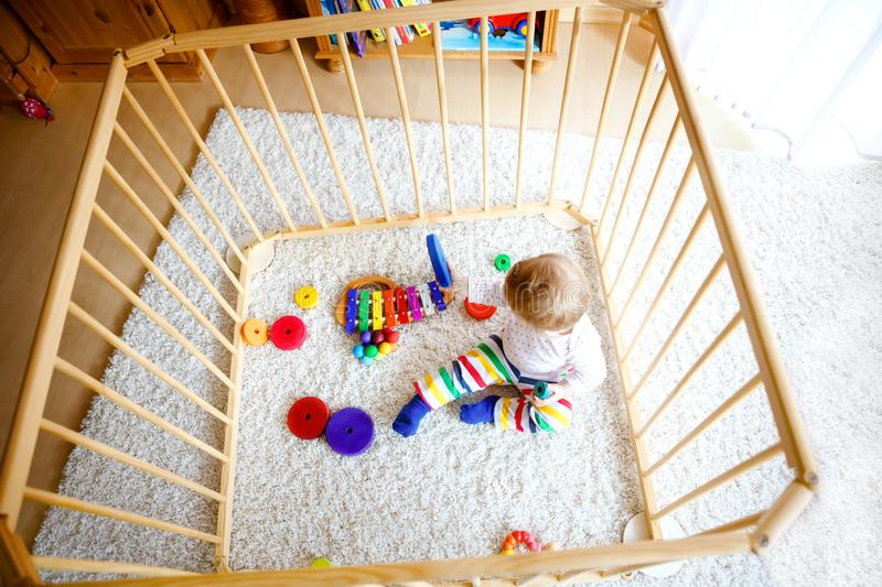 Beautiful little baby girl standing inside playpen. Cute adorable child playing with colorful toys. Home or nursery stock image