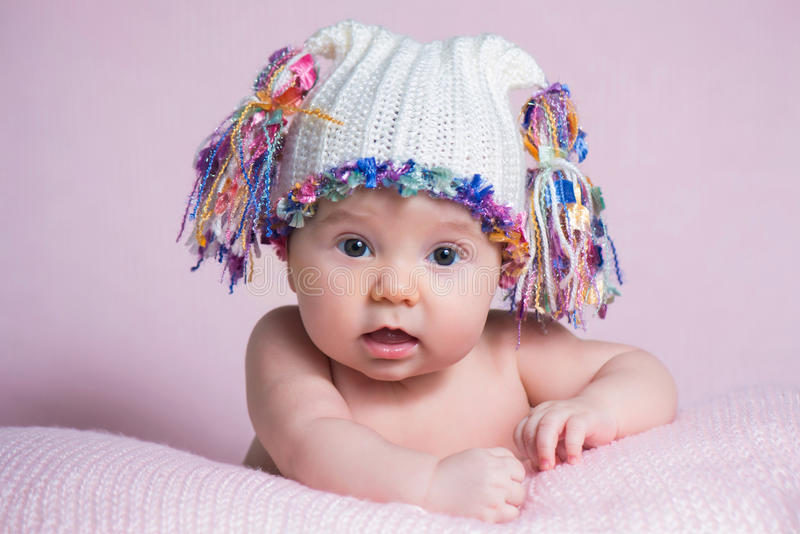Beautiful little baby girl wearing pink knitted cap stock photo