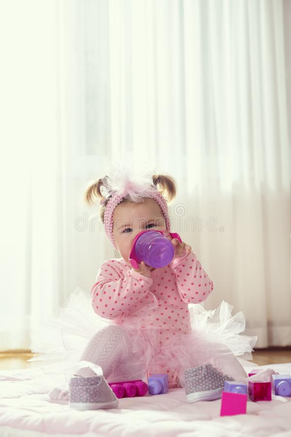 Baby girl drinking water from a bottle royalty free stock image