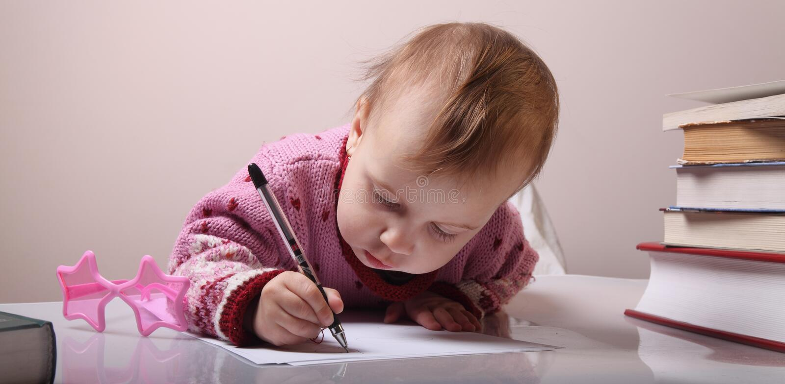 Beautiful little baby girl is writing letter royalty free stock photo