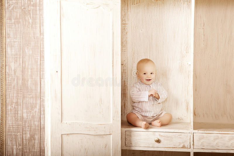 Beautiful little baby sitting in the closet. Smiling child and i. Beauty little baby sitting in the closet. Smiling child and interior of a bedroom. Cute kid stock photos