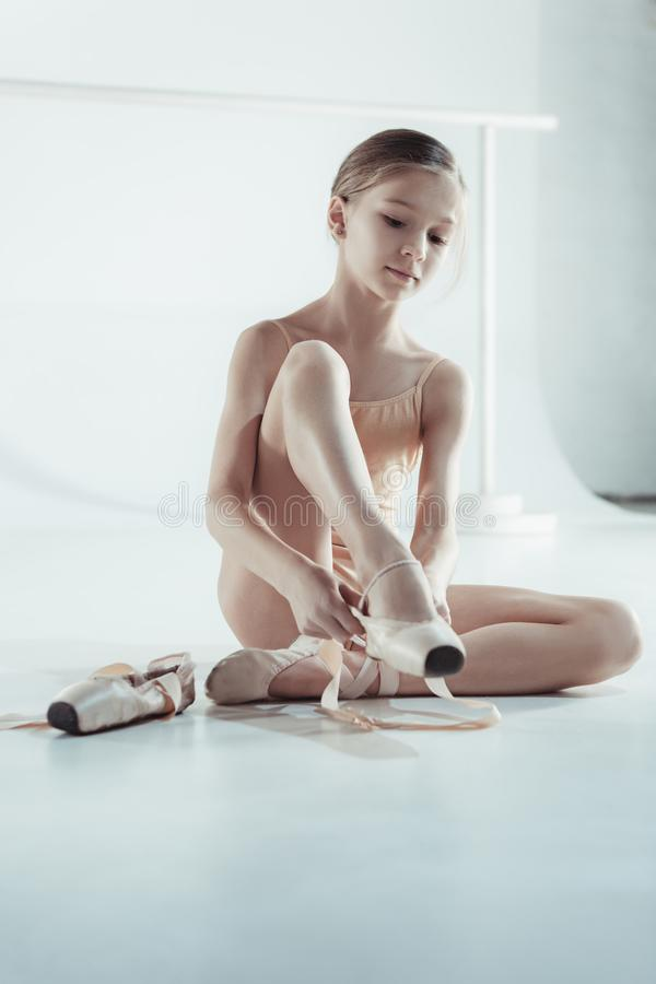 Beautiful little ballerina in blue dress for dancing puting on foot pointe shoes royalty free stock photography