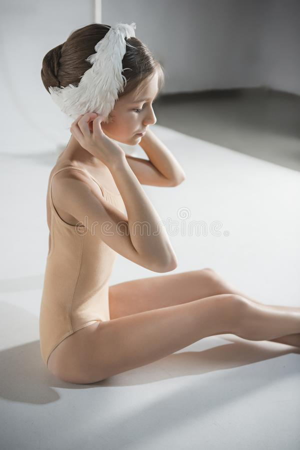Beautiful little ballerina wearing a white swan bandage on her head. Beautiful little ballerina sitting on the floor and wearing a white swan bandage on her head royalty free stock photos