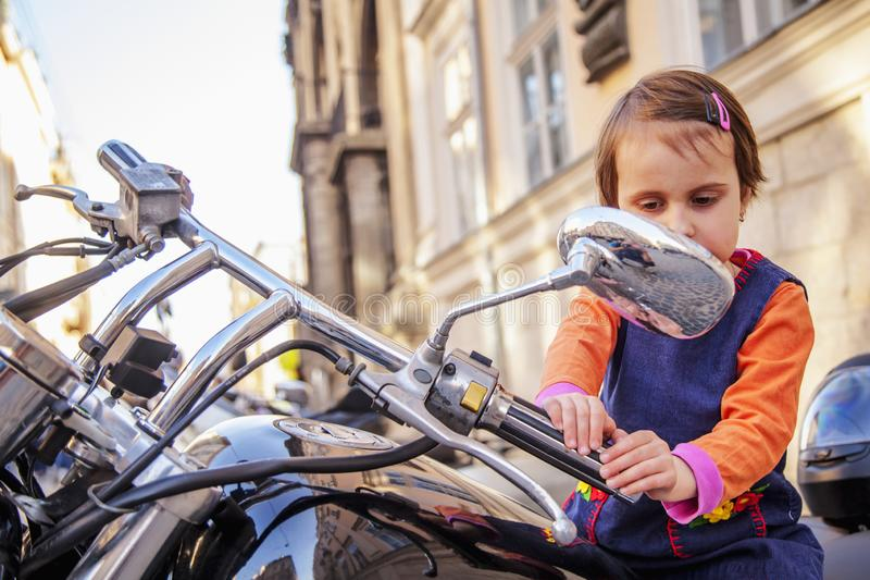 Beautiful little biker child girl on a motorcycle as a symbol of freedom, adventure and travel. Humorous photography royalty free stock image