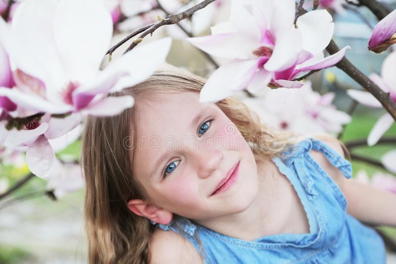 Beautiful little blond girl in blue dress holding flowers of magnolia under blossom magnolia tree. stock images