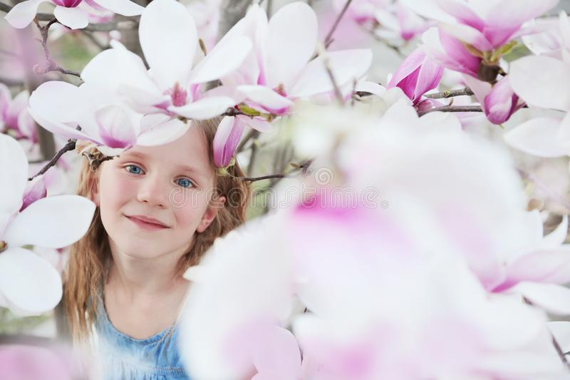 Beautiful little blond girl in blue dress holding flowers of magnolia under blossom magnolia tree. royalty free stock photos