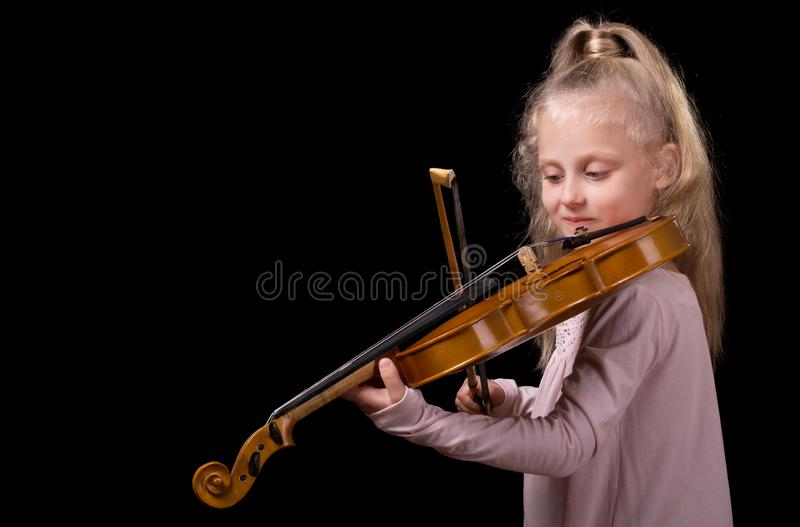Beautiful little blond girl playing the violin isolated on black background royalty free stock photo
