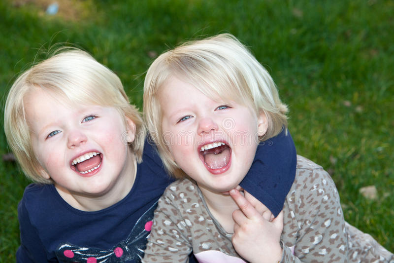 Beautiful little blond identical twins girls stock photo