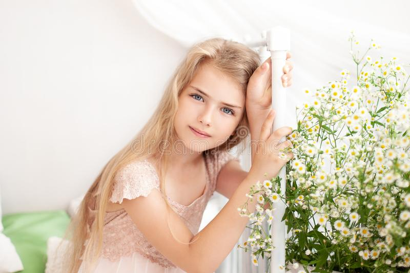 Beautiful little blonde girl with long hair sits on a bed with a bouquet of daisies in a bright white bedroom with a rustic interi royalty free stock images