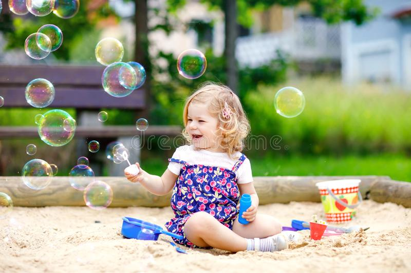 Beautiful little blonde toddler girl having fun with blowing soap bubble blower. Cute adorable baby child playing on royalty free stock image