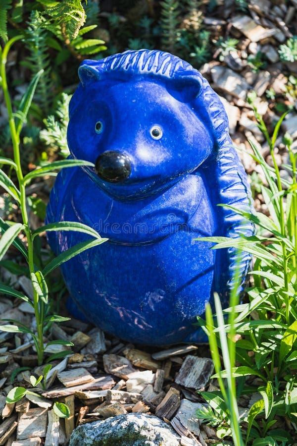 Beautiful little blue garden statue of a hedgehog stock photo