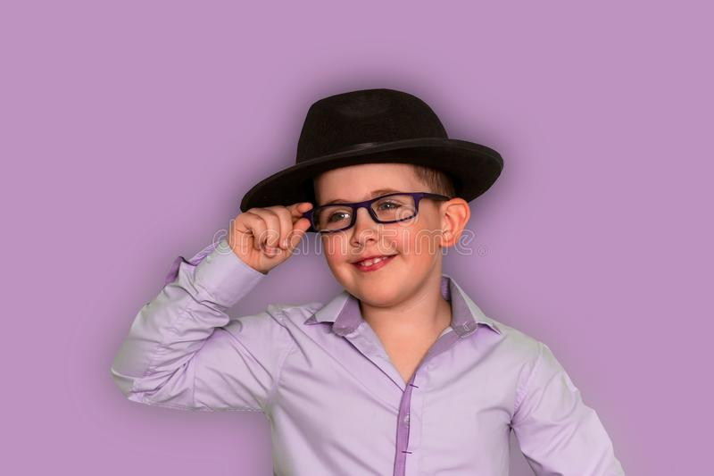 little boy in black hat and purple shirt holding hand on glasses, purple background royalty free stock image