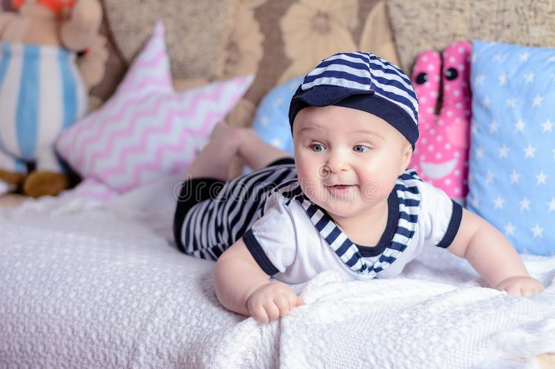 A beautiful little boy in a costume sailor lays on a bed near the pillows stock image