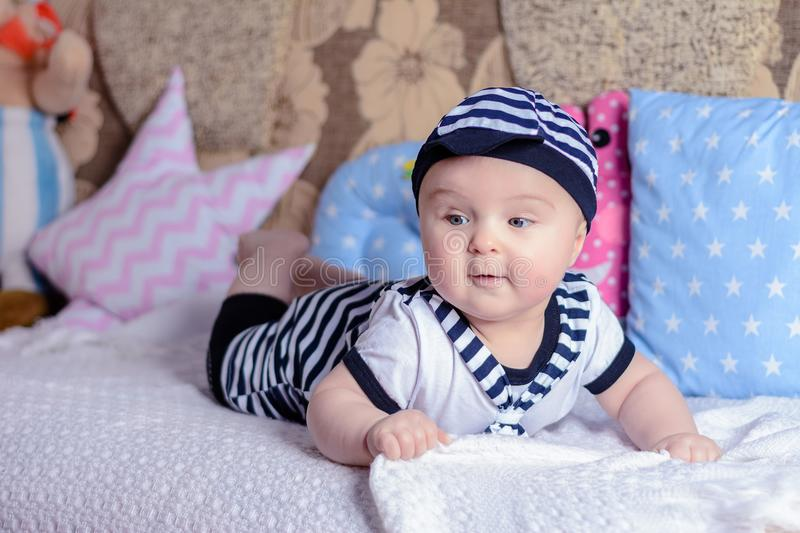 A beautiful little boy in a costume sailor lays on a bed near the pillows royalty free stock image