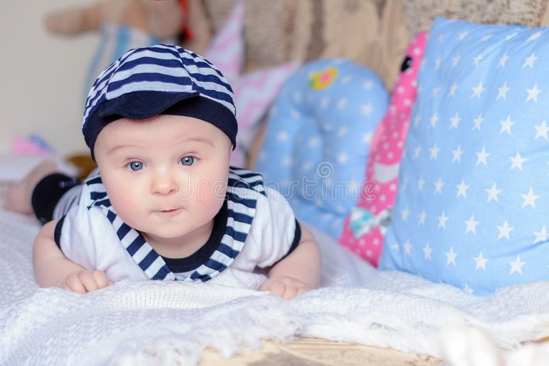 A beautiful little boy in a costume sailor lays on a bed near the pillows royalty free stock photo