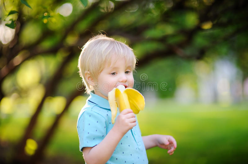Beautiful little boy eating banana during picnic in summer sunny park royalty free stock image