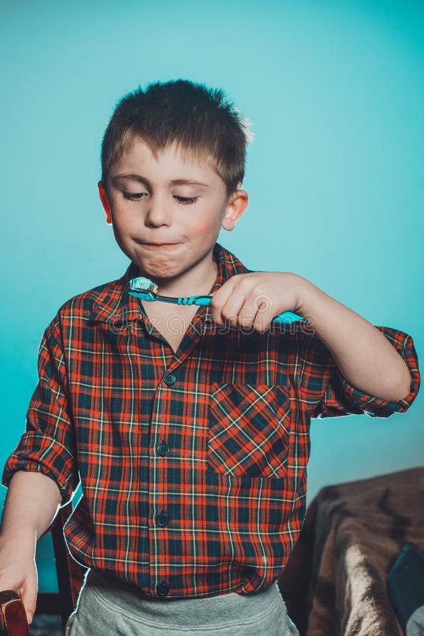 A beautiful little boy in a pajamas smiles and holds in his hand a toothbrush on a blue background royalty free stock photo