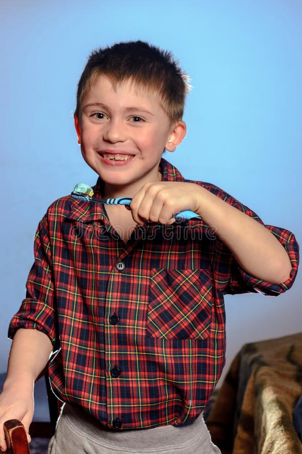 A beautiful little boy in a pajamas smiles and holds in his hand a toothbrush on a blue background stock photo