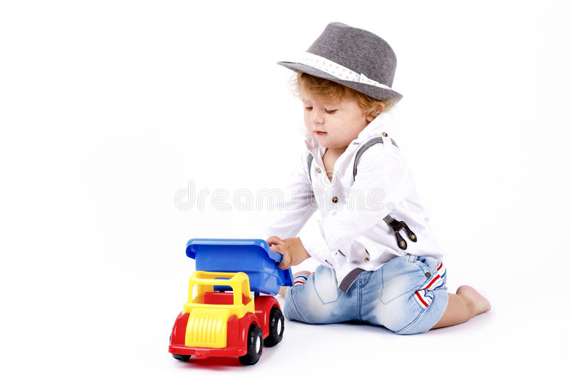 Beautiful little boy playing with car. Beautiful little boy sitting on the floor and playing with car, studio portrait stock photo