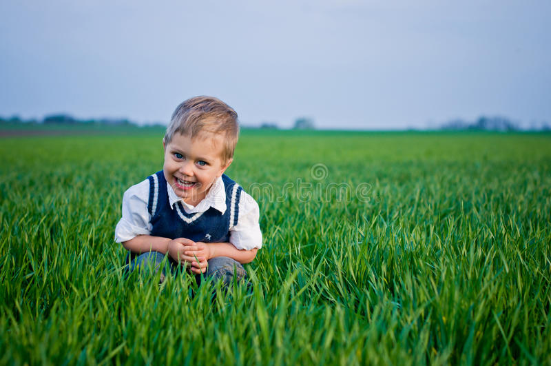 A beautiful little boy sitting in the grass stock photos