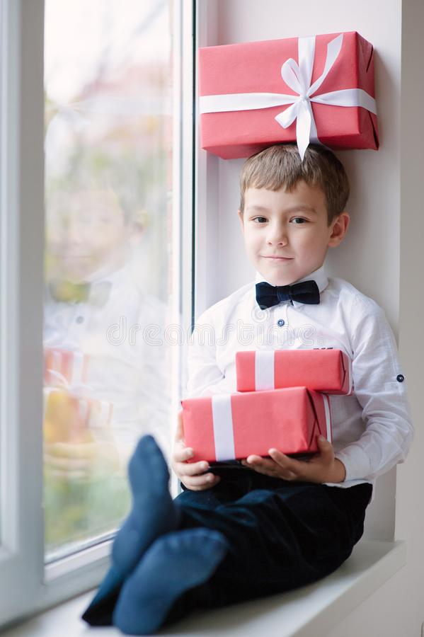 Cute little boy sitting by the window with a gift box on head stock photo