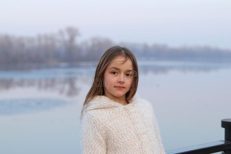 Beautiful little brown-eyed girl in white coat looking at camera seriously stock images