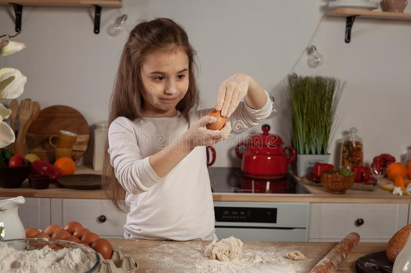 Beautiful little girl dressed in a white blouse is making a dough for baking a bread at a kitchen. stock image