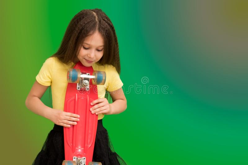 The child is holding a skateboard. Interested in sports, the concept of the modern teenager. Beautiful little brunette girl with skateboard stock image