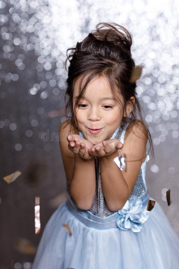 Beautiful little child girl in silver and blue dress with confetti. Beautiful happy little child girl in blue dress with confetti on background with silver bokeh stock image