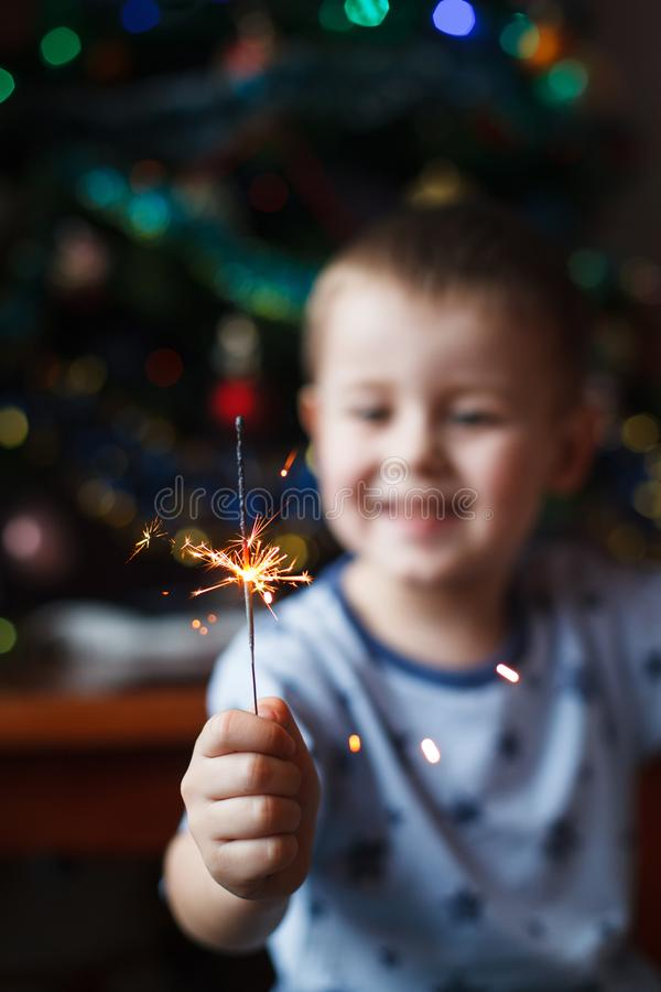 Beautiful Little child holding burning sparkler on New Year`s Eve, bengal fire. Select focus on fireworks. Happy boy holding royalty free stock images