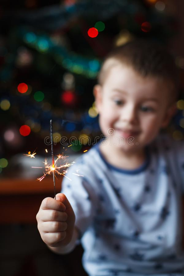 Beautiful Little child holding burning sparkler on New Year`s Eve, bengal fire. Select focus on fireworks. Happy boy holding royalty free stock photos