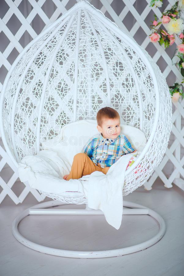 A beautiful little boy sits on a swing and poses for a photographer stock photos