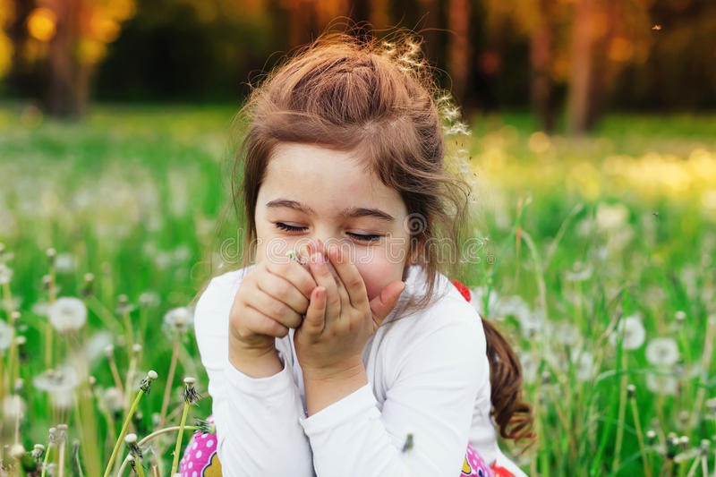 Beautiful little child smiling with dandelion flower in sunny summer park. Happy cute kid having fun outdoors at sunset. stock photos
