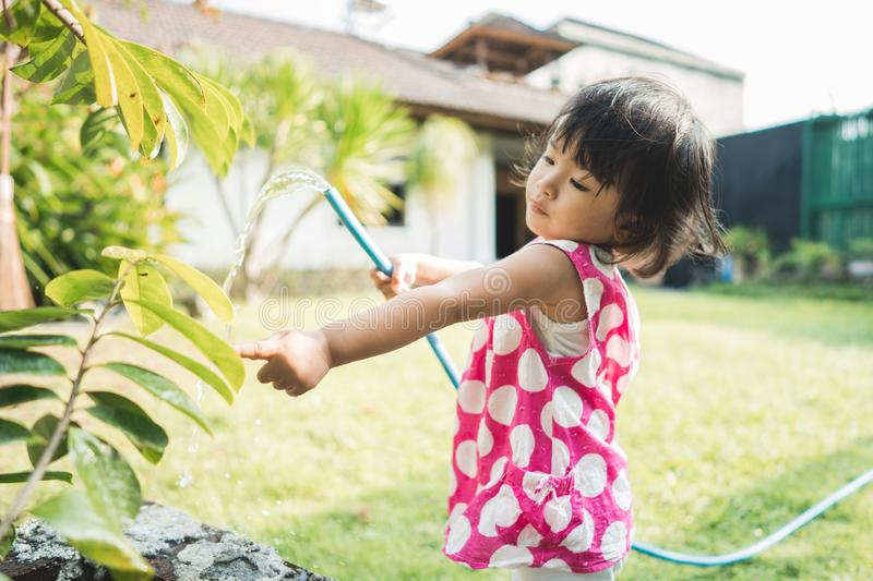 Beautiful little child watering the plants royalty free stock images