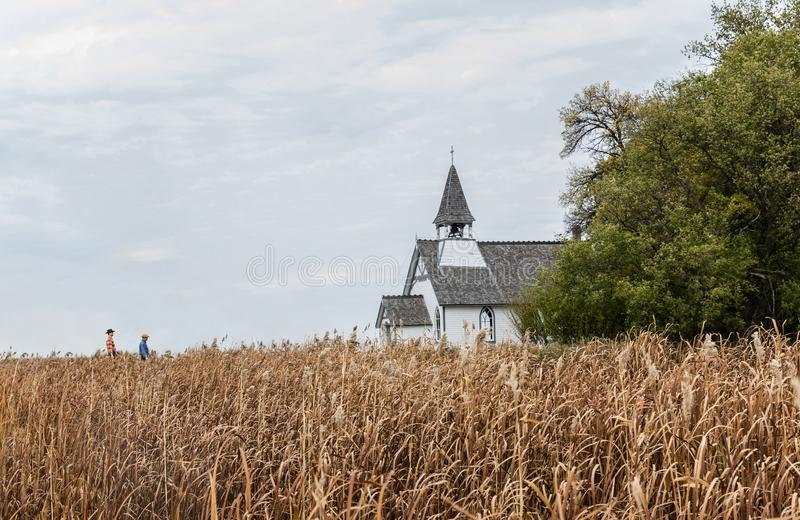 Beautiful little country church sitting behind a golden barley field. Horizontal distant full length image of two caucasian cowboys walking toward a beautiful stock photography