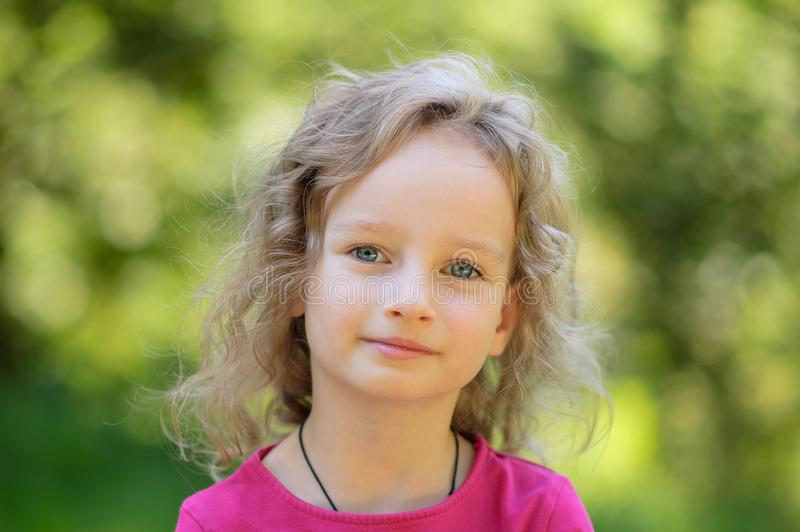 Beautiful little curly blonde girl, has happy fun cheerful smiling face, big blue eyes, long eyelashes. Portrait in wood royalty free stock photography