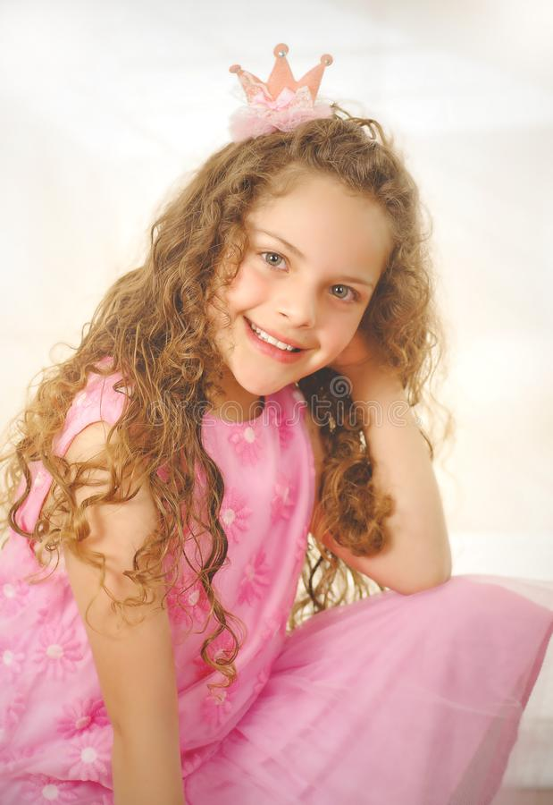 Beautiful little curly girl posing for camera and wearing a pink princess dress stock image