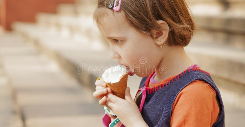 Beautiful little cute child girl eating ice cream in the summer food, dessert, childhood, satisfaction, carelessness concept royalty free stock photo