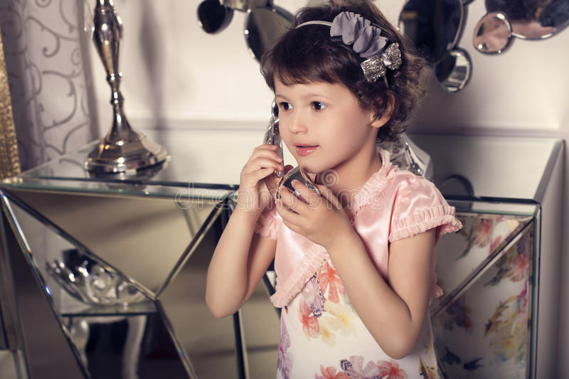 Beautiful little cute girl speaking by telephone royalty free stock image