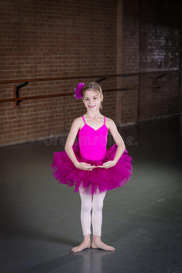 Beautiful little dancer portrait at a dance studio. Beautiful little dancer ballerina portrait at a dance studio. Vertical photo in a traditional dance studio stock image