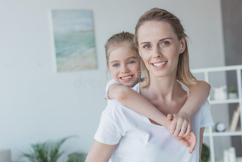 beautiful little daughter piggybacking on her stock images