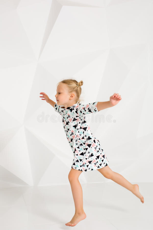 Beautiful little fashion model on white studio background. Portrait of cute girl posing in studio. Little blonde in bright summer dress royalty free stock photography